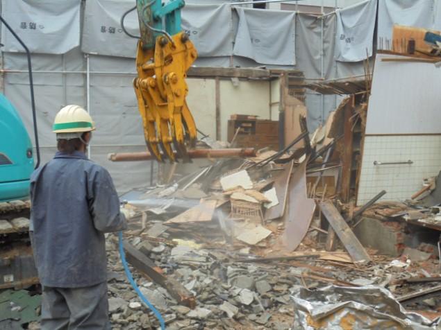 家屋解体中、ホコリを抑えるため散水しながら作業する。
